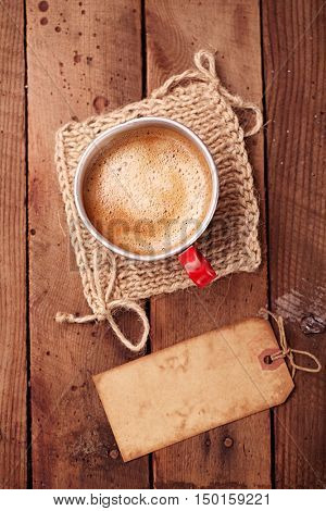 coffee in unusual vintage tin mug with grunge paper tag on old wood