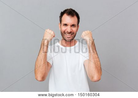 Happy excited young casual man celebrating success over grey background