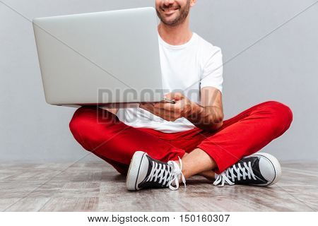 Cropped image of a happy smiling casual man sitting on the floor with laptop over gray background