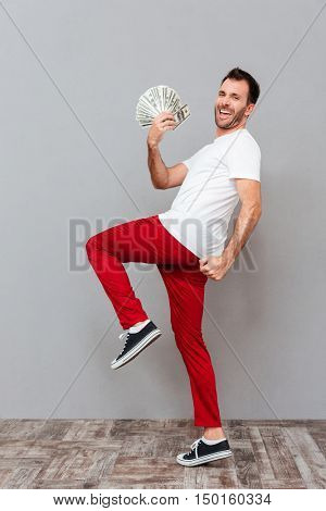Full length portrait of a cheerful excited young man holding dollars and celebrating success over gray background