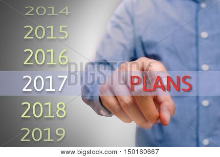 Man hand pointing plans text Body man businessman planing work for 2017. Business new year plans and targets concept.