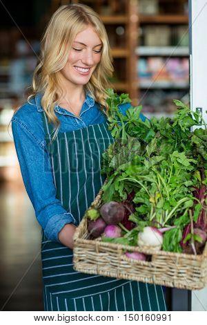 Smiling female staff holding a basket of fresh vegetables in supermarket?