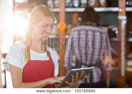 Smiling female staff using digital tablet in supermarket