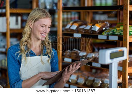 Smiling female staff looking at clipboard in super market