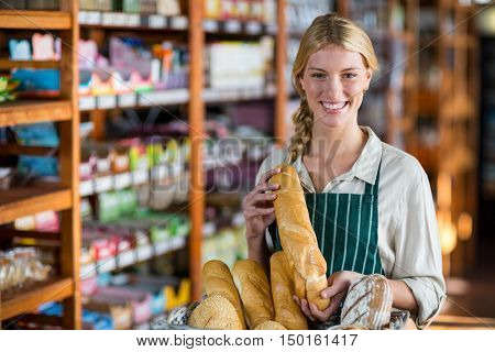 Portrait of happy female staff holding loaf of bread at bread counter in supermarket