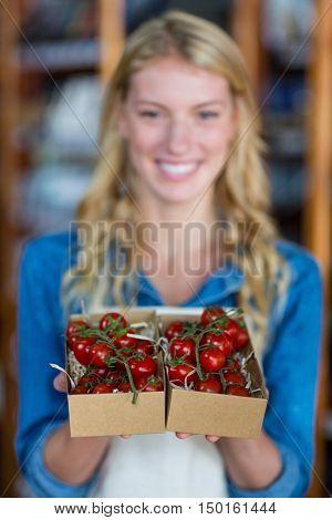 Portrait of smiling female staff holding box of cherry tomato in super market