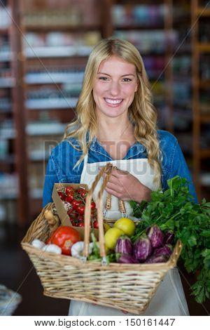 Portrait of smiling female staff holding basket of vegetables in organic section of supermarket