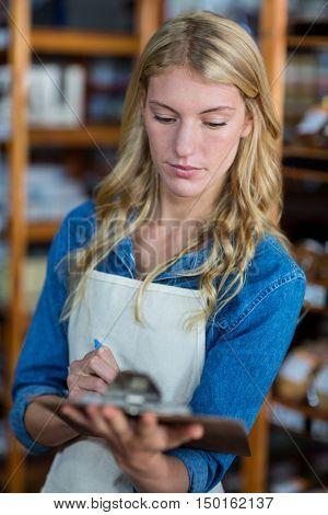 Female staff writing on clipboard in super market