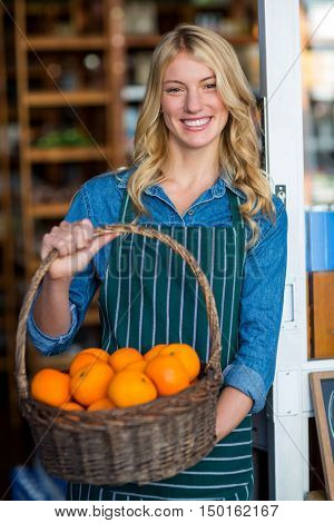 Portrait of smiling female staff holding basket of fruit in organic section of supermarket