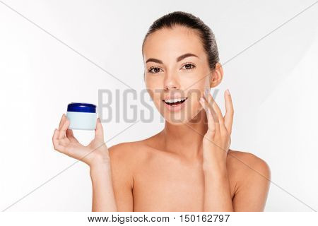 Young woman putting cream on her face isolated on white background