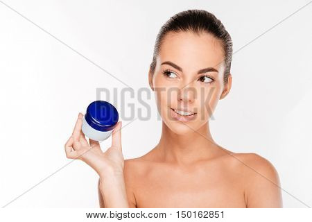Attractive young woman holding cream bottle isolated on a white background