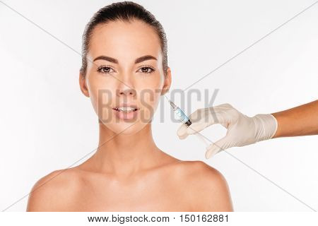 Beautiful young woman gets beauty injection in eye area with syringe isolated on white background