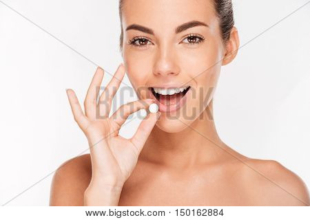 Beauty portrait of a pretty young woman holding pill isolated on white background
