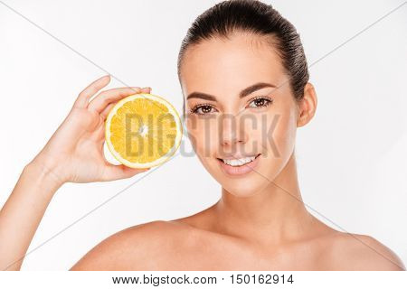 Portrait of attractive smiling woman holding half of orange isolated on a white background