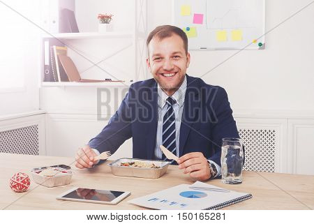 Man has healthy business lunch in modern office interior. Young happy handsome businessman at working place with tablet, with vegetable salad in bowl, diet and eating right concept.