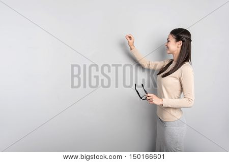 Look here children. Positive delighted professional teacher standing near board and writing on it while conducting a lesson