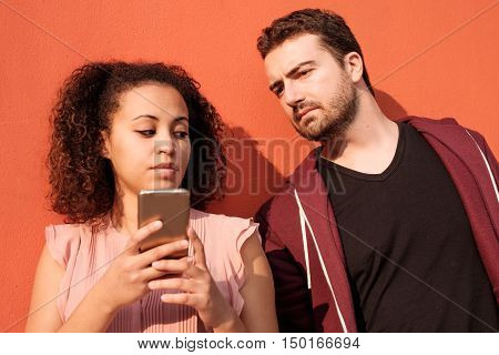 Jealous man spying his girlfriend mobile phone