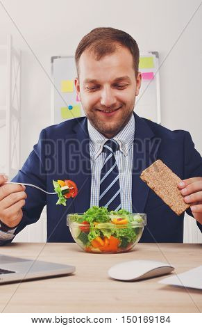 Man has healthy business lunch in modern office interior. Young handsome businessman at working place, looking at plate with vegetable salad in bowl, diet and eating right concept. Vertical