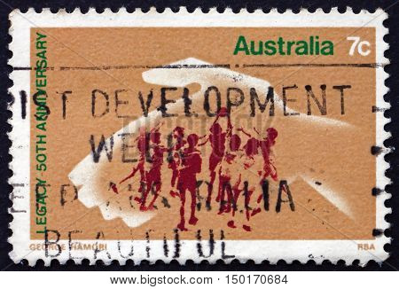AUSTRALIA - CIRCA 1973: a stamp printed in Australia shows Hand Protecting Playing Children 50th Anniversary of Legacy an ex-servicemen's Organization circa 1973