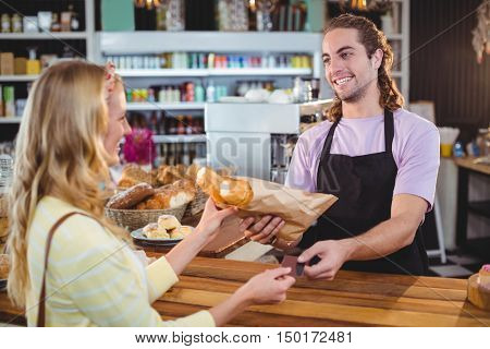 Waiter giving bread roll to customer at counter in caf?