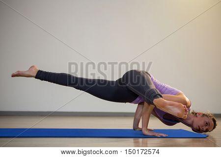 Woman doing eka pada koundinyasana on exercise mat in fitness studio