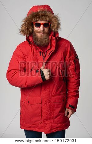 smiling bearded man in red winter jacket showing thumb up gesture, over grey background