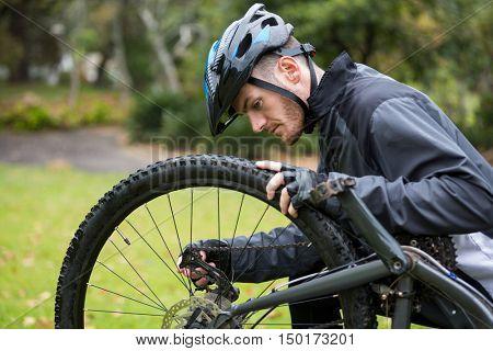 Male cyclist repairing his mountain bike in park