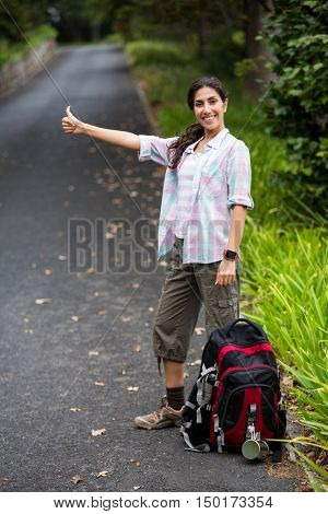 Woman hitch hiking on the road in the countryside