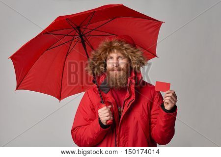 Man in red winter jacket standing under umbrella and showing blank credit card, over grey background