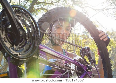 Woman fixing her bike in a forest in the countryside