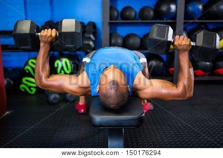 Young man exercising with dumbbells on weight bench in fitness studio