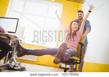 Portrait of young businessman pushing cheerful female colleague sitting in chair at creative office