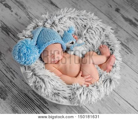 lovely newborn in blue hat with pompom and toy on round bed with furry blanket, top view