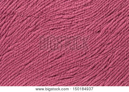 Dark pink background from a soft wool textile material closeup. Fabric with natural texture. Cloth backdrop.