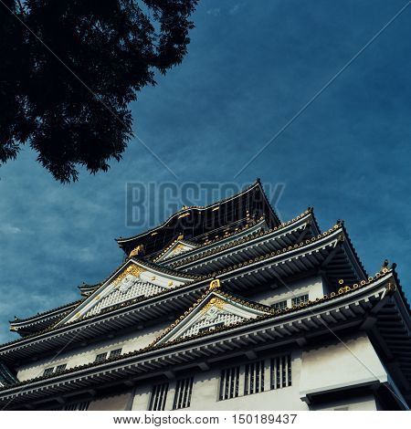 Osaka Castle with silhouette of  tree against blue sky. June 2016