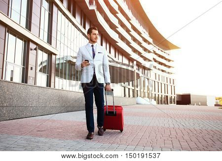 Young happy traveler businessman making call after arriving at hotel outside with his luggage. Smiling traveler using smartphone