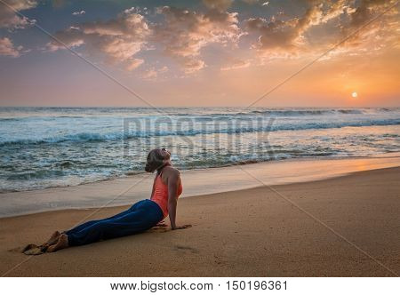 Yoga outdoors on beach - woman practices Ashtanga Vinyasa yoga Surya Namaskar Sun Salutation asana Urdhva Mukha Svanasana - upward facing dog pose on sunset