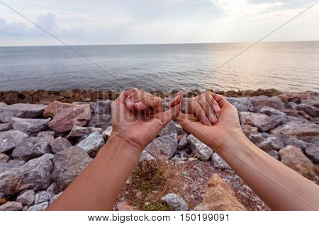 Lover be nands in hands against the sky with silhouette background. Hands in shape of love heart.