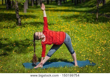 Pregnancy yoga exercise - pregnant woman doing asana Utthita trikonasana outdoors on grass in summer