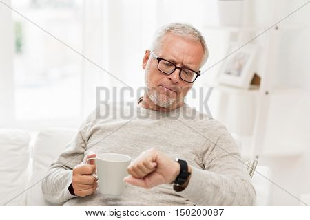 time, morning and people concept - senior man with cup of tea looking at wristwatch at home