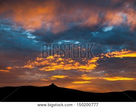 Dramatic sunset sky with illuminated clouds in the mountains. Dark black silhouette of mountain ridge and Jested transmitter tower at the bottom.