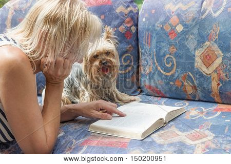 Blond woman is reading a book together with a Yorkshire terrier who is sitting on the couch in front of open book. The dog with his tongue hanging out is looking at the camera.