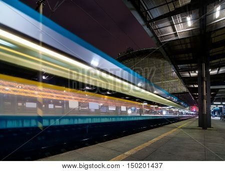 Train Speeding Through Prague Railway Station During Busy Night Time With Extended Motion. Beautiful