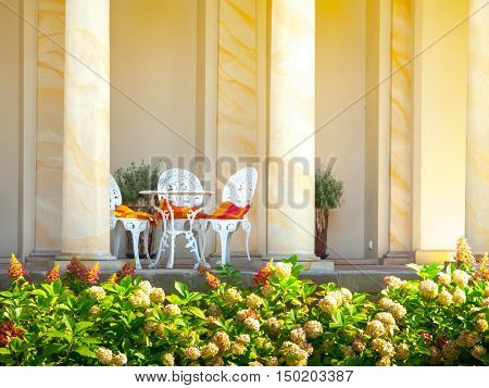 Romantic set of table and white chairs in a garden archway cafe or restaurant. Prefect beautiful place for relax or romantic date - rendez vous.