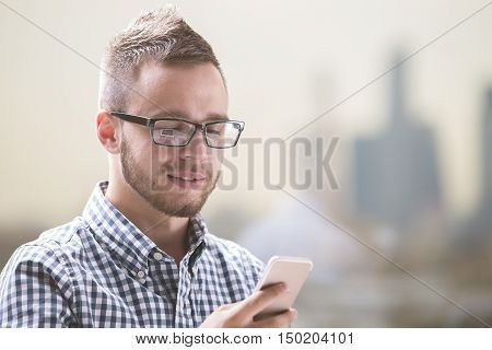 Closeup portrait of young european businessman in casual shirt and glasses using cellular phone at workplace