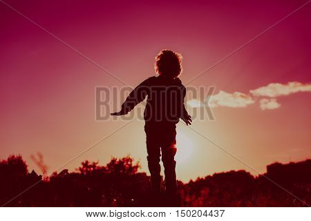 happy little boy jumping from joy in sunset nature
