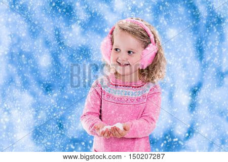 Little girl in pink knitted sweater and fur earwarmer catching snowflakes in winter park. Kids play outdoor in snowy forest. Children catch snow flakes. Toddler kid playing outside in snow storm.