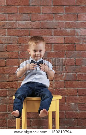Stylish little gentleman in a bow tie sitting on a yellow table on a brick wall background