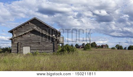 Wooden barn, timber building in the farmland. Agriculture in rural countryside. Farmland and crop in the landscape. Electrical lines.