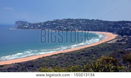 Palm Beach one of Sydney's iconic northern beaches. Barrenjoey lighthouse dividing Pittwater from Tasman Sea Sydney NSW Australia. Coast headland panorama with bay and surrounding green mountains.